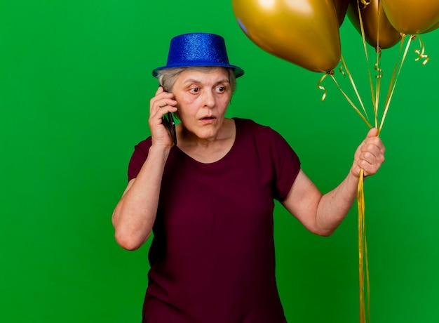 Angstige oudere vrouw met feestmuts houdt helium ballonnen praten over de telefoon op groen
