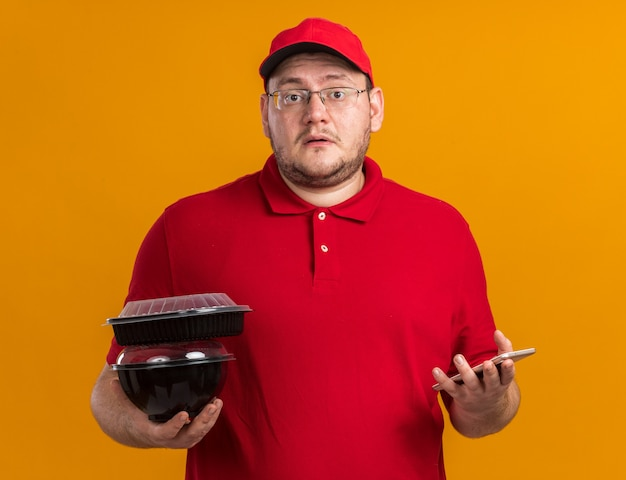 Angstige overgewicht jonge bezorger in optische bril met voedselcontainers en telefoon geïsoleerd op oranje muur met kopieerruimte