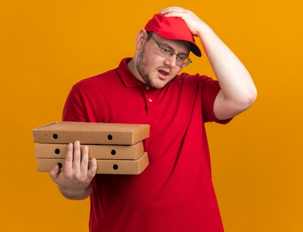Angstige overgewicht jonge bezorger in optische glazen pizzadozen te houden en hand op het hoofd te zetten geïsoleerd op oranje muur met kopie ruimte