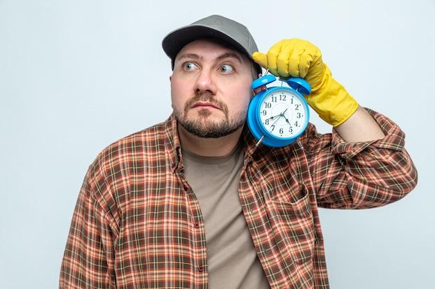 Angstige schonere man met rubberen handschoenen die een wekker vasthoudt en naar de zijkant kijkt
