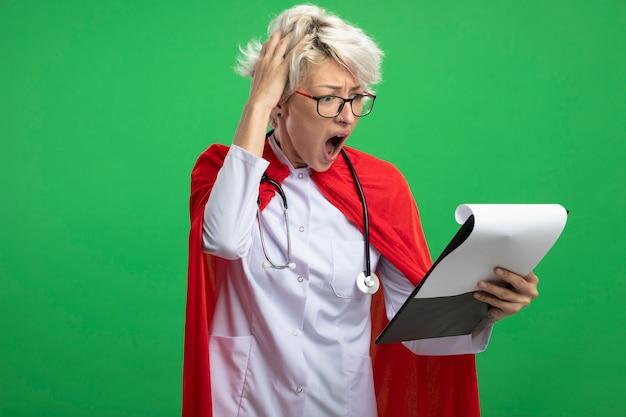 Angstige slavische superheld vrouw in uniform van de arts met rode cape en stethoscoop in optische bril legt hand op het hoofd en kijkt naar klembord geïsoleerd op groene muur met kopie ruimte