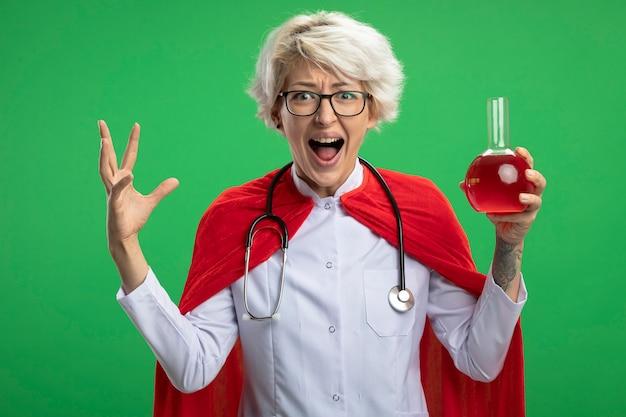 Angstige slavische superheldvrouw in doktersuniform met rode cape en stethoscoop in optische glazen staat met opgeheven hand en houdt rode chemische vloeistof in glazen kolf op groene muur
