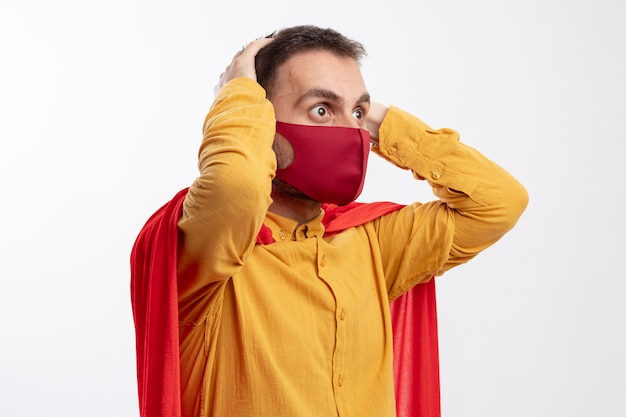 Angstige superheld man met rode mantel dragen rood masker legt handen op het hoofd kijken kant geïsoleerd op een witte muur