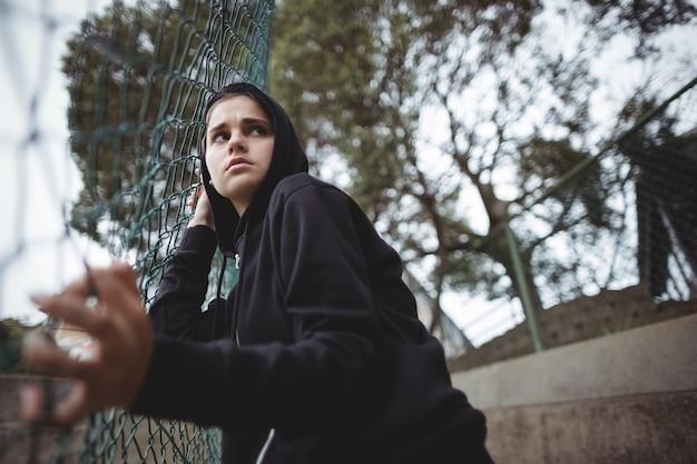 Angstige tiener die op de omheining van het draadnetwerk leunt