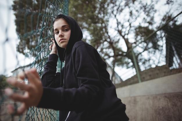 Angstige tiener die op de omheining van het draadnetwerk op schoolcampus leunt