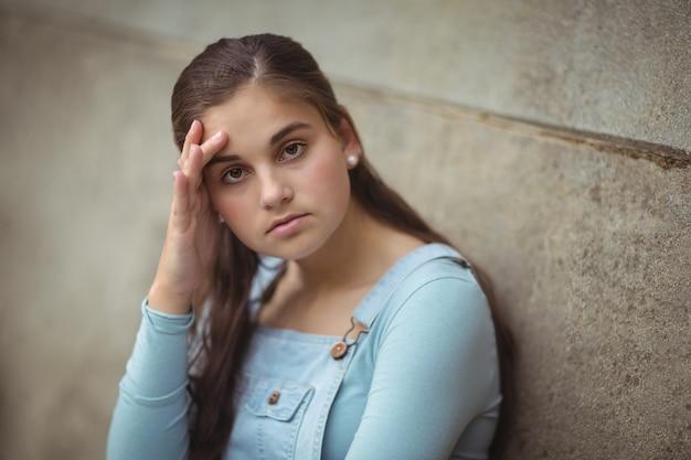 Angstige tiener die op muur leunt