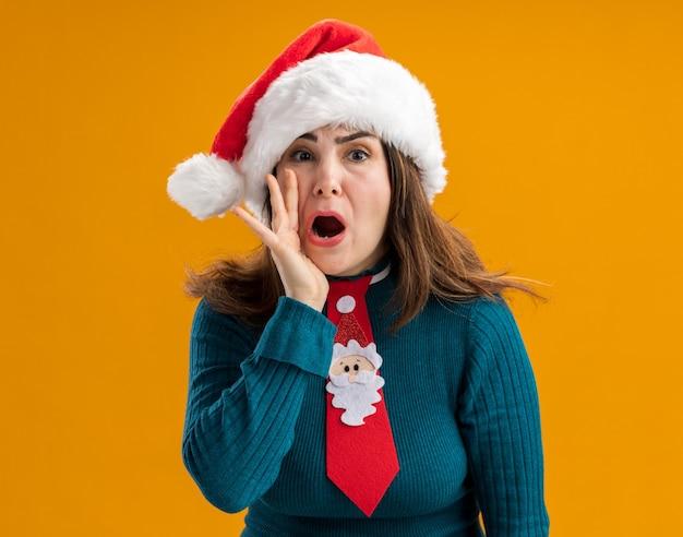 Angstige volwassen blanke vrouw met kerstmuts en kerststropdas houdt de hand dicht bij de mond en roept iemand geïsoleerd op een oranje muur met kopieerruimte