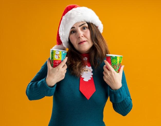 Angstige volwassen blanke vrouw met kerstmuts en kerststropdas met papieren bekers geïsoleerd op een oranje muur met kopieerruimte