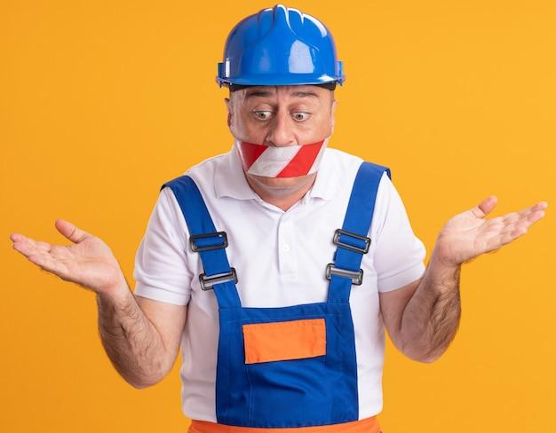Angstige volwassen bouwer man in uniform heeft betrekking op mond met duct tape en houdt handen open neerkijkt geïsoleerd op oranje muur