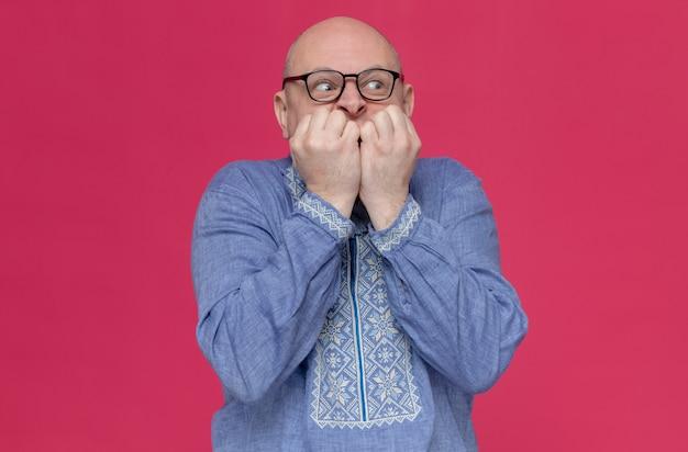 Angstige volwassen man in blauw shirt met een bril die op zijn nagels bijt en naar de zijkant kijkt