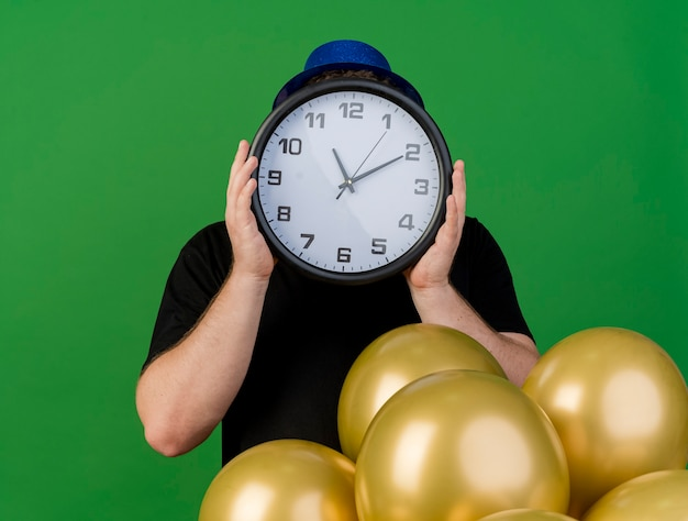 Angstige volwassen man in optische bril met blauwe feestmuts houdt klok voor gezicht en staat met helium ballonnen geïsoleerd op groene muur