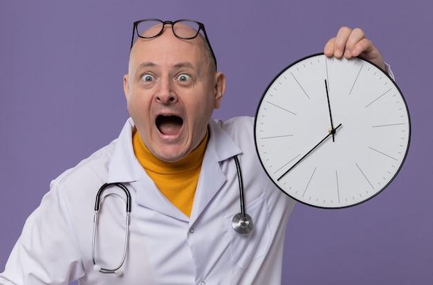 Angstige volwassen man met bril in doktersuniform met stethoscoop die klok vasthoudt en naar de zijkant kijkt