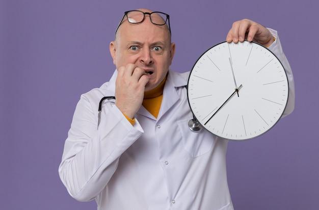 Angstige volwassen man met bril in doktersuniform met stethoscoop die klok vasthoudt en op zijn nagels bijt