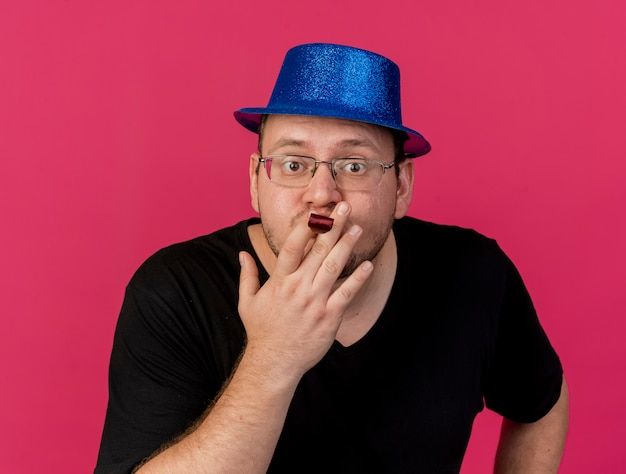 Angstige volwassen slavische man met een optische bril met een blauwe feestmuts die een feestfluitje blaast