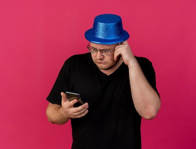 Angstige volwassen slavische man met een optische bril met een blauwe feestmuts houdt de telefoon vast en kijkt naar