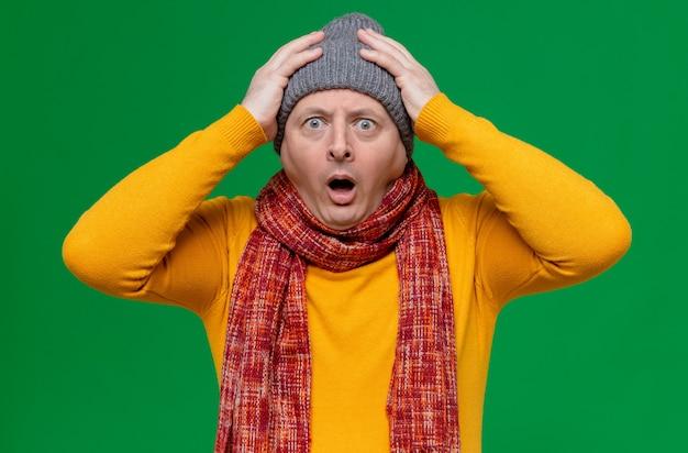 Angstige volwassen slavische man met wintermuts en sjaal om zijn nek die handen op zijn hoofd legt en naar voren kijkt