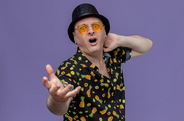 Angstige volwassen slavische man met zwarte hoge hoed met een zonnebril die zijn hand uitstrekt en kijkt