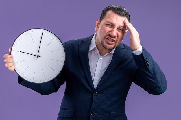 Angstige volwassen slavische zakenman die klok vasthoudt en hand op zijn voorhoofd legt