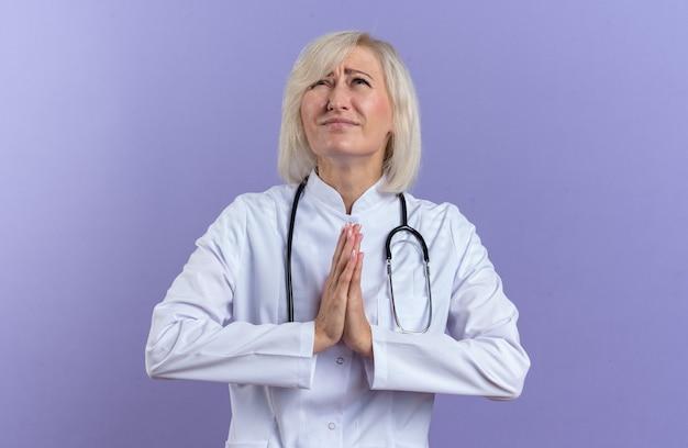 Angstige volwassen vrouwelijke arts in medisch gewaad met stethoscoop hand in hand samen biddend en opzoekend geïsoleerd op paarse muur met kopieerruimte
