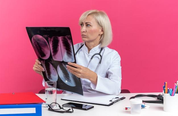 Angstige volwassen vrouwelijke arts in medische gewaad met stethoscoop zittend aan een bureau met kantoorhulpmiddelen die röntgenresultaat houden en naar de zijkant kijken geïsoleerd op roze muur met kopieerruimte