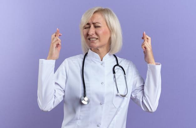 Angstige volwassen vrouwelijke arts in medische mantel met stethoscoop die vingers kruist geïsoleerd op paarse muur met kopieerruimte