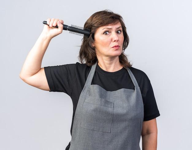 Angstige volwassen vrouwelijke kapper in uniform die kam vasthoudt en naar de voorkant kijkt geïsoleerd op een witte muur met kopieerruimte