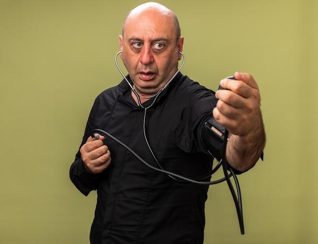 Angstige volwassen zieke blanke man die druk meet met bloeddrukmeter geïsoleerd op olijfgroene muur met kopieerruimte