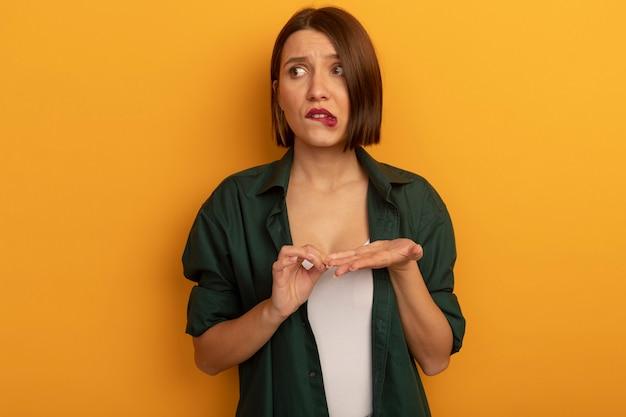 Angstige vrij blanke vrouw bijt lippen en kijkt naar de zijkant op oranje