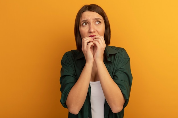 Angstige vrij blanke vrouw bijt nagels kant kijken op oranje
