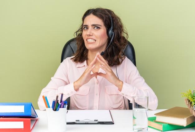Angstige, vrij blanke vrouwelijke callcenter-operator op koptelefoon zittend aan bureau met kantoorhulpmiddelen geïsoleerd op groene muur