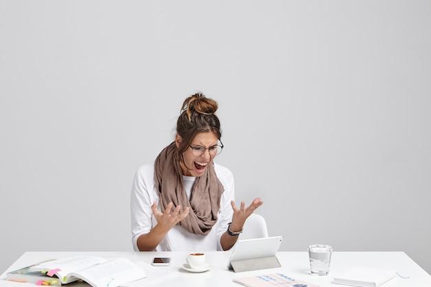 Angstige vrouw kijkt naar tablet, realiseert zich dat ze het project niet heeft opgeslagen en alles vanaf het begin moet doen