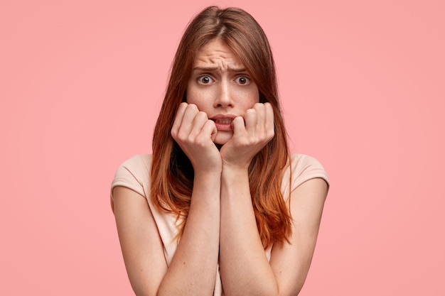 Angstige vrouw met sproeten op het gezicht, kijkt met angstige uitdrukking draagt casual gestreept t-shirt, geïsoleerd op een roze achtergrond.