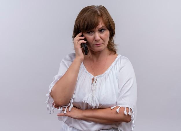 Angstige vrouw op middelbare leeftijd die mobiele telefoon aan oor op geïsoleerde witte muur zet