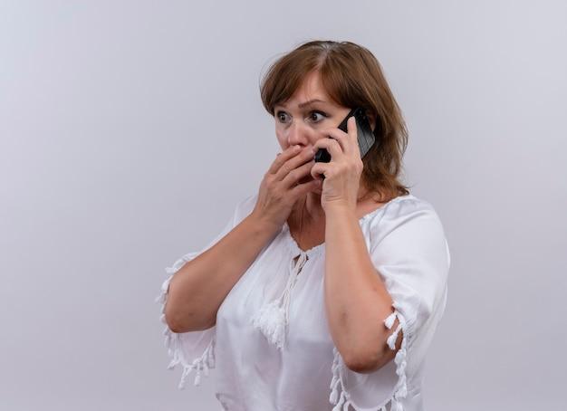 Angstige vrouw van middelbare leeftijd die op telefoon spreekt en hand op haar mond op geïsoleerde witte muur legt