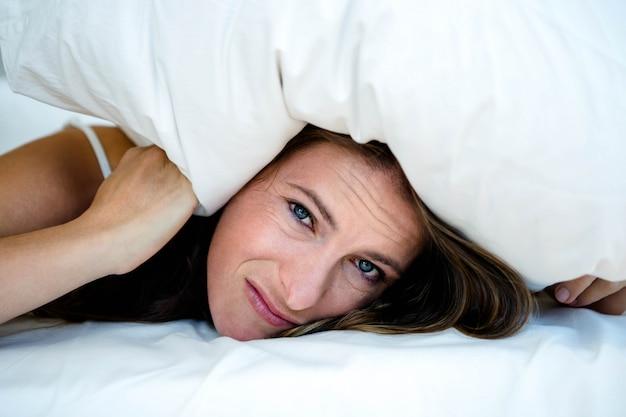 Angstige vrouw verstopt onder een kussen, liggend op haar bed