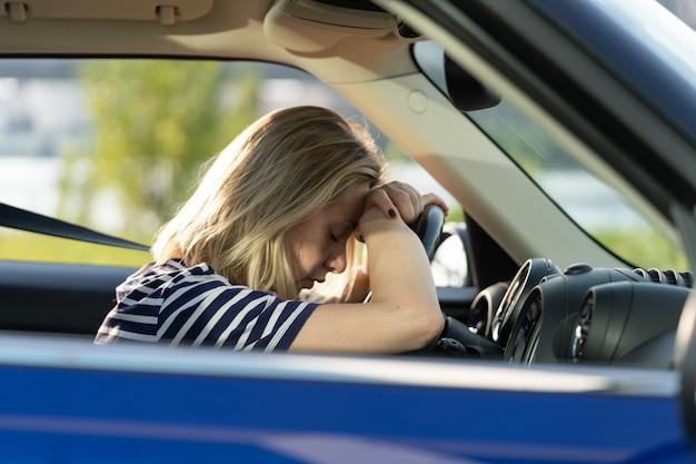 Angstige vrouwelijke bestuurder in auto lijdt aan paniekaanval huilen gefrustreerd ongelukkig volwassen vrouwelijk rijdend voertuig