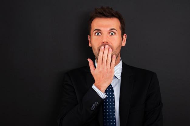 Angstige zakenman die zijn mond behandelt