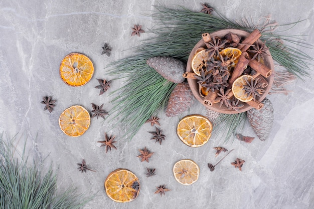 Anijs en kaneel met stukjes sinaasappel in een houten beker