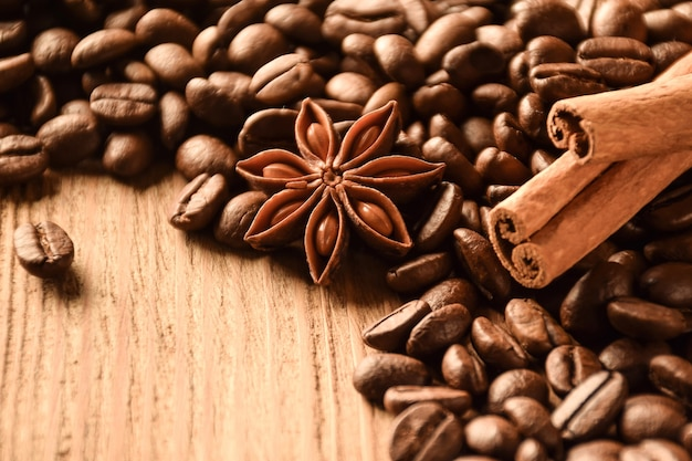 Anijs, kaneel en veel koffiebonen liggen op een bruin houten tafel.