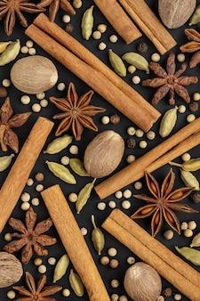 Anijs kardemom kaneelbroodjes nootmuskaat peperkorrels een set van kruiden op een zwarte achtergrond backgro