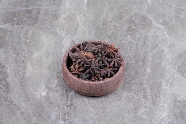 Anijsbloemen in een houten kop op het marmer