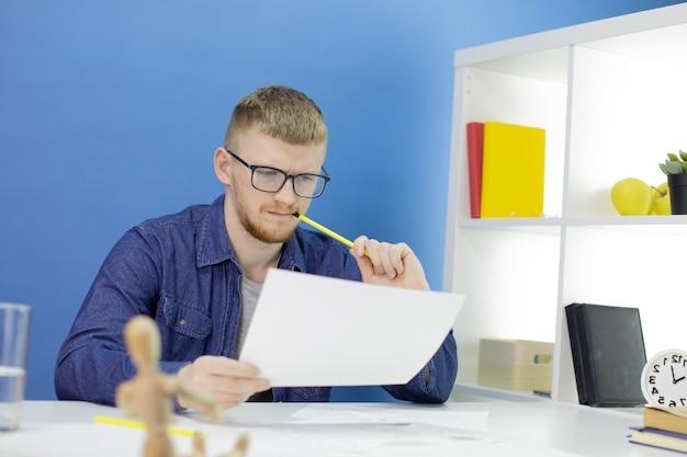 Animator-ontwerper in creatief proces, het maken van helden, tekent potloodschetsen
