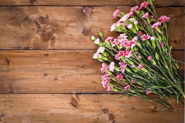 Anjer met roze en witte bloemblaadjes op een houten tafel
