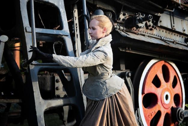 Anna karenina-stijl - mooie vrouw met retro jurk en hoed en kapsel in de buurt van het oude treinstation zoals geschreven in de dramatische roman van leo tolstoj