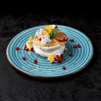 Anna pavlova cake met lemon curd en fruit.