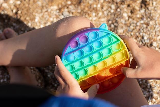 Anoniem kind speelt met fidget pop het op het strand nieuw zintuiglijk speelgoed voor kinderen en volwassenen