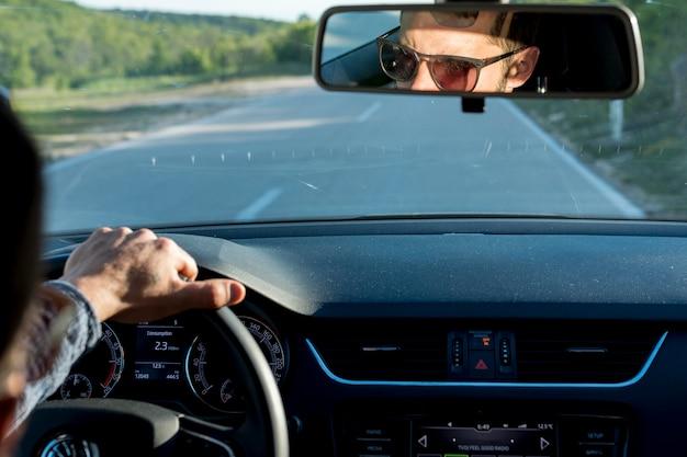 Anoniem mannetje dat met auto op zonnige dag reist