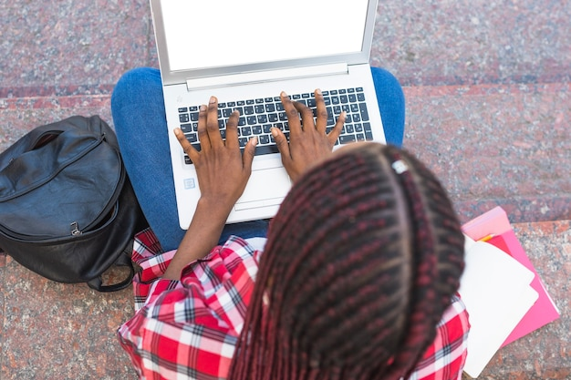 Anoniem meisje met behulp van laptop op de trap