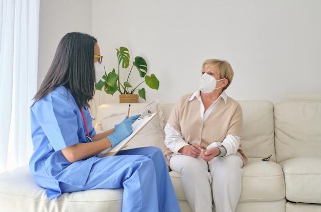 Anonieme arts die thuis met patiënt in ademhalingsmasker spreekt