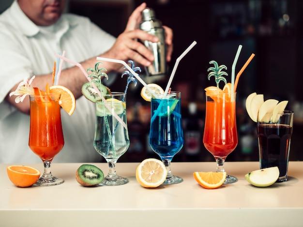 Anonieme barman die dranken in shaker mengt en heldere glazen serveert